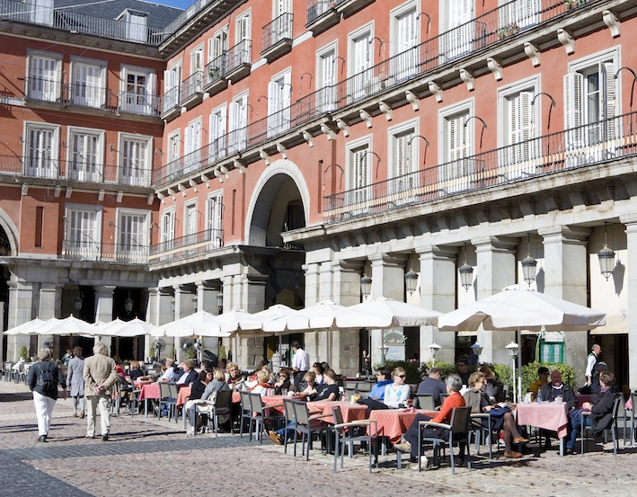 people sitting at cafes at the plaza Mayor Madrid